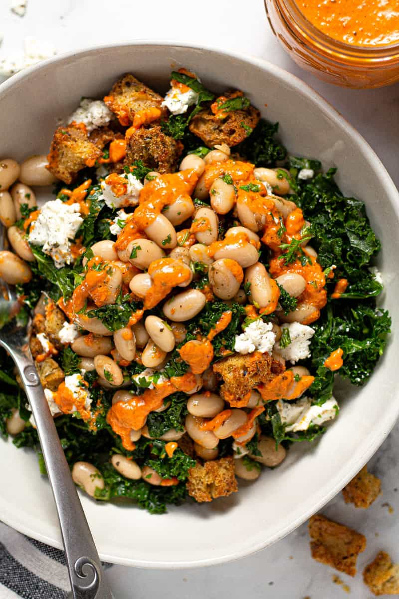 Overhead shot of a massaged kale salad with white beans and tomato dressing