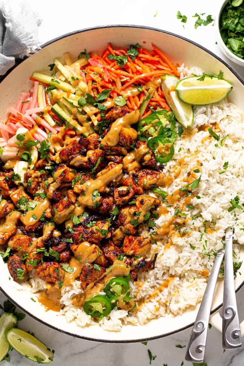 Overhead shot of a large white pan filled with Thai chicken and rice drizzled with peanut sauce