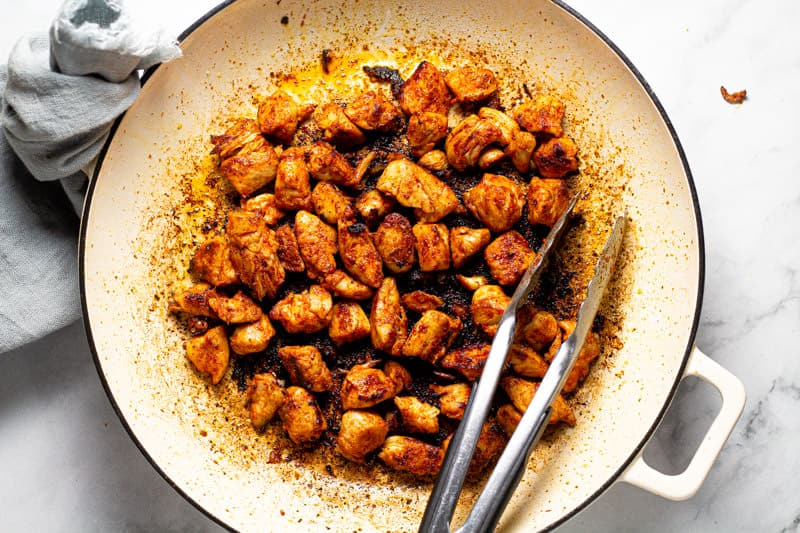 Large white pan with sauteed diced chicken breast