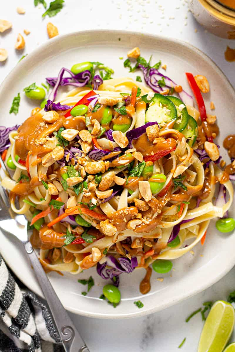 Plate filled with vegan peanut pasta salad garnished with green onions