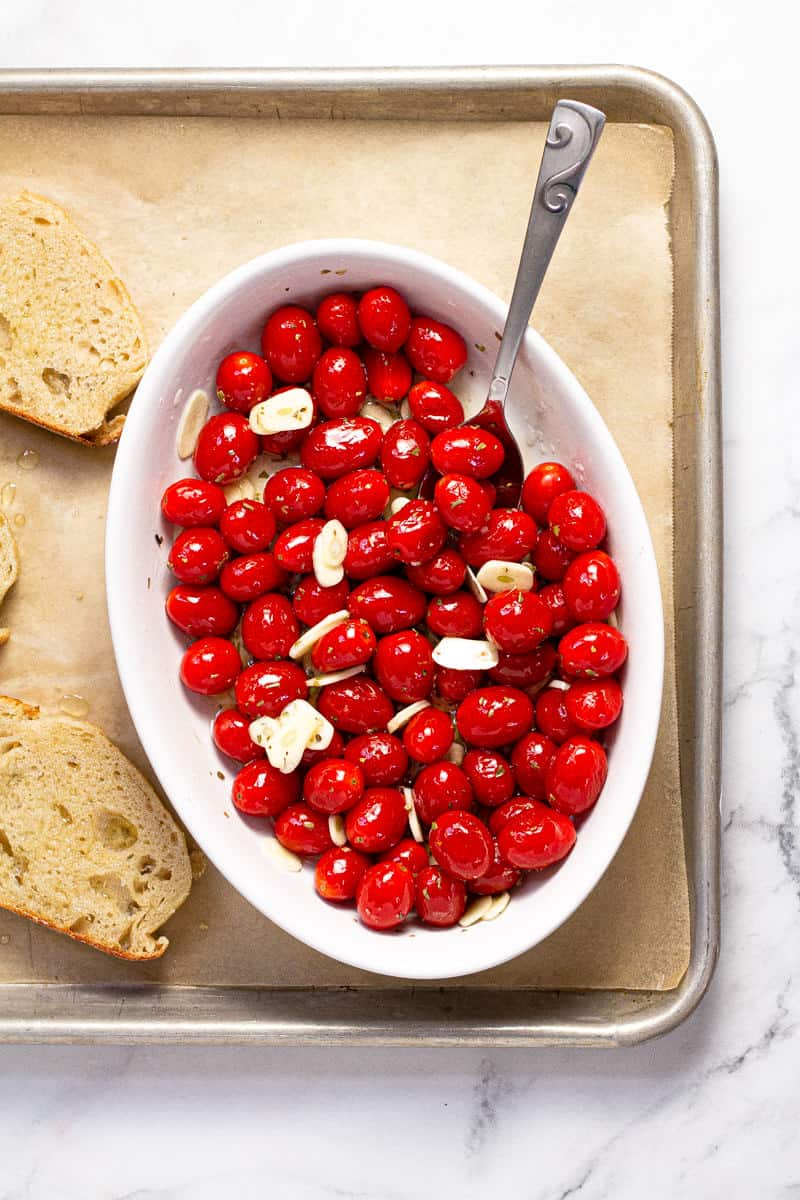White baking dish with grape tomatoes tossed in olive oil with garlic