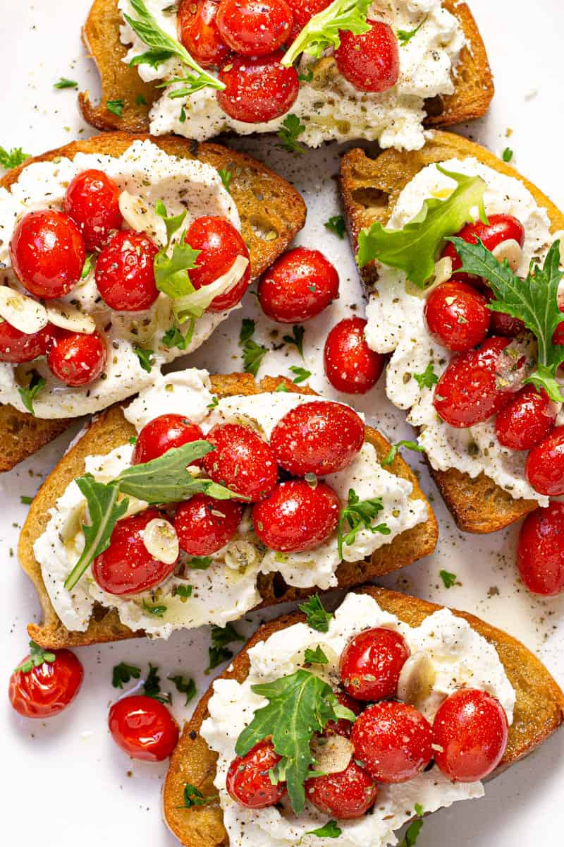 Overhead shot of roasted tomatoes on toast with ricotta and arugula