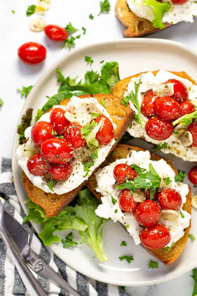 White plate with roasted tomato toasts spread with ricotta garnished with greens