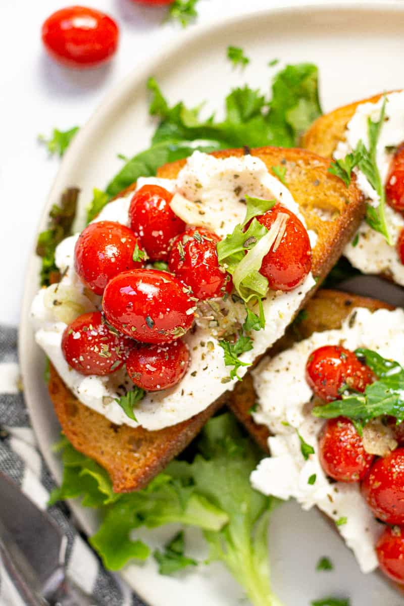 Close up shot of roasted tomato toast spread with ricotta