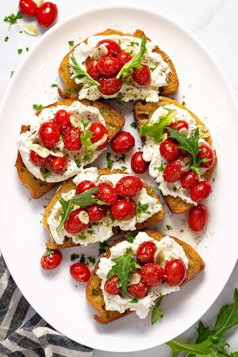 Large white platter with roasted tomatoes and garlic on top of toast with ricotta and greens