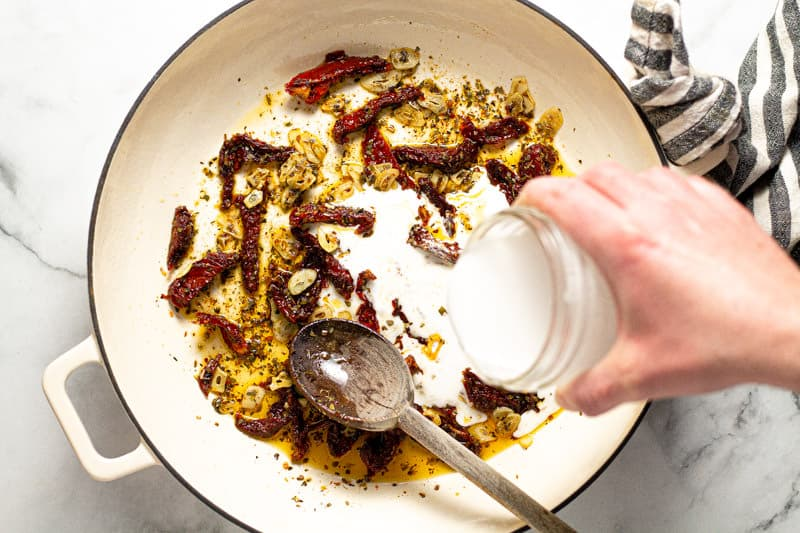 A hand pouring coconut milk into a pan of sun dried tomatoes and garlic