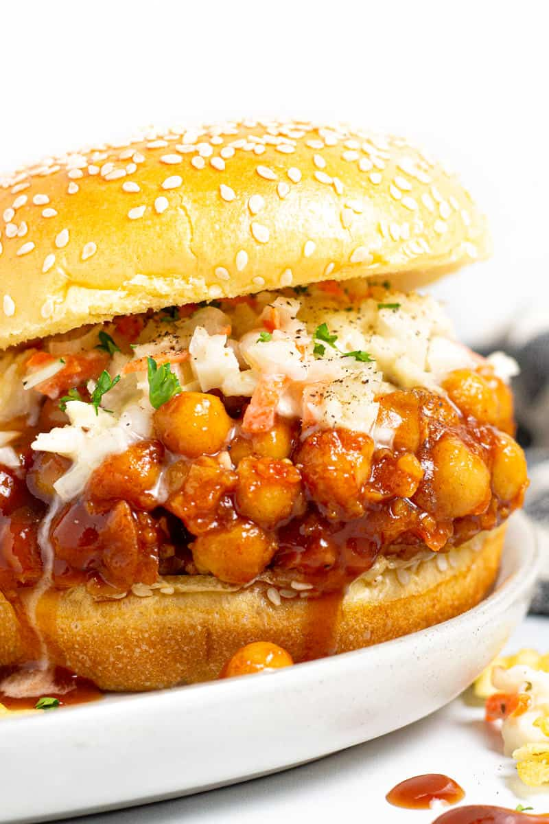 Close up shot of a BBQ chickpea sandwich dripping with barbecue sauce