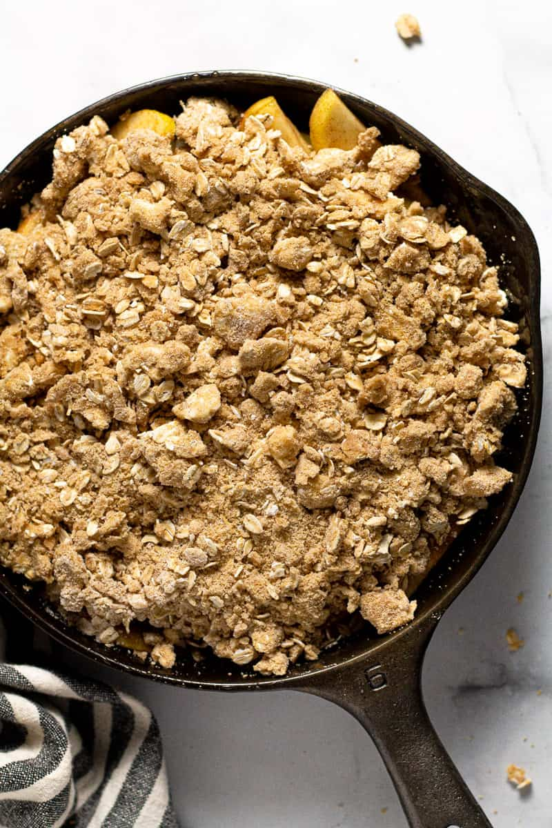 Cast iron skillet with homemade apple crisp ready to go in the oven