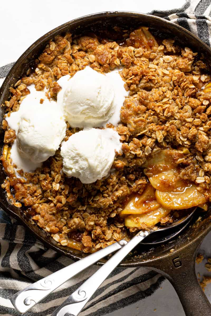 Large cast iron skillet filled with homemade apple crisp topped with vanilla ice cream