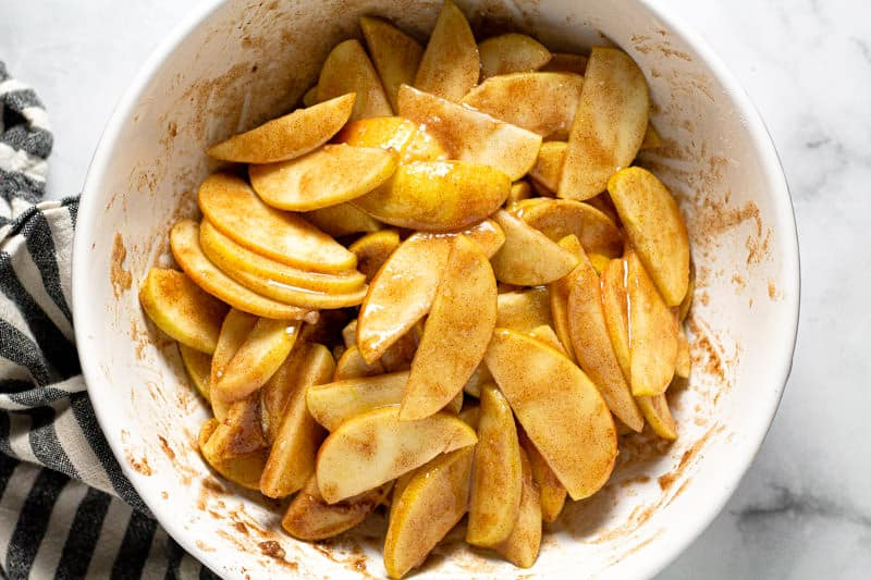 Large white bowl filled with ingredients to make apple crisp filling