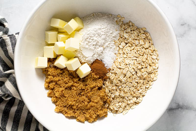 Large white bowl filled with ingredients to make apple crisp topping
