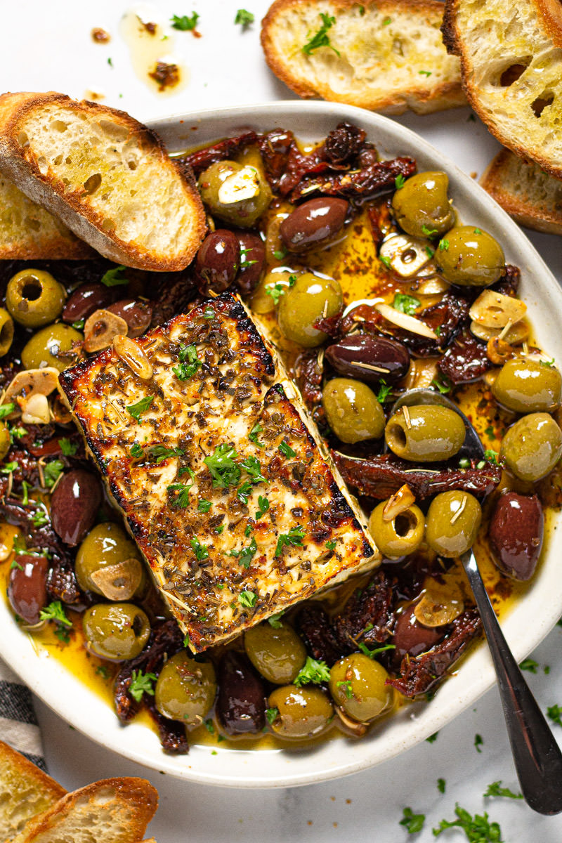 White plate filled with baked feta olives and herbs