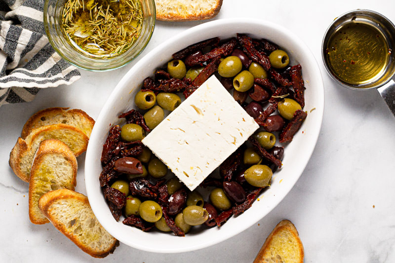 Small white baking dish with olives, sun dried tomatoes and a block of feta in it