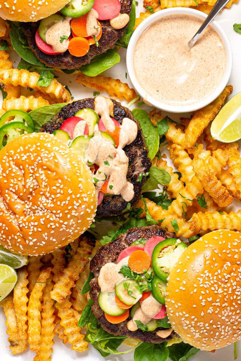 Large white platter filled with three Banh Mi burgers and crispy baked fries
