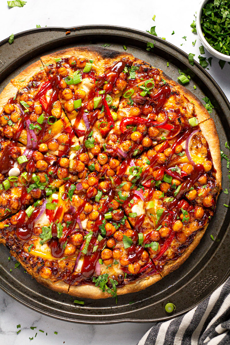 Round pizza pan with homemade chickpea veggie pizza garnished with cilantro