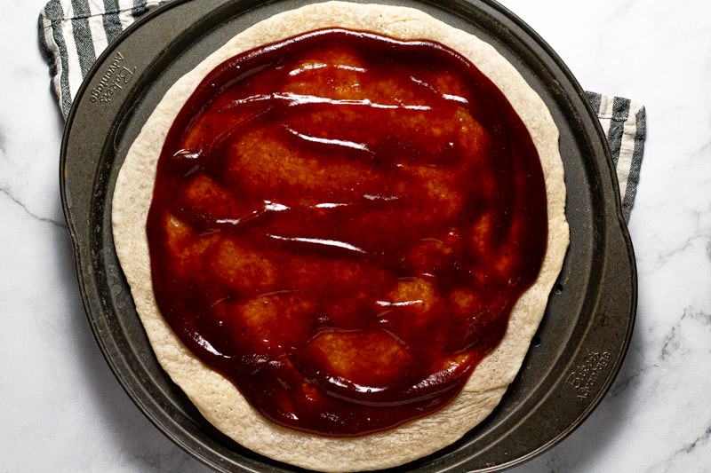 Round pizza pan with pizza crust spread with barbecue sauce