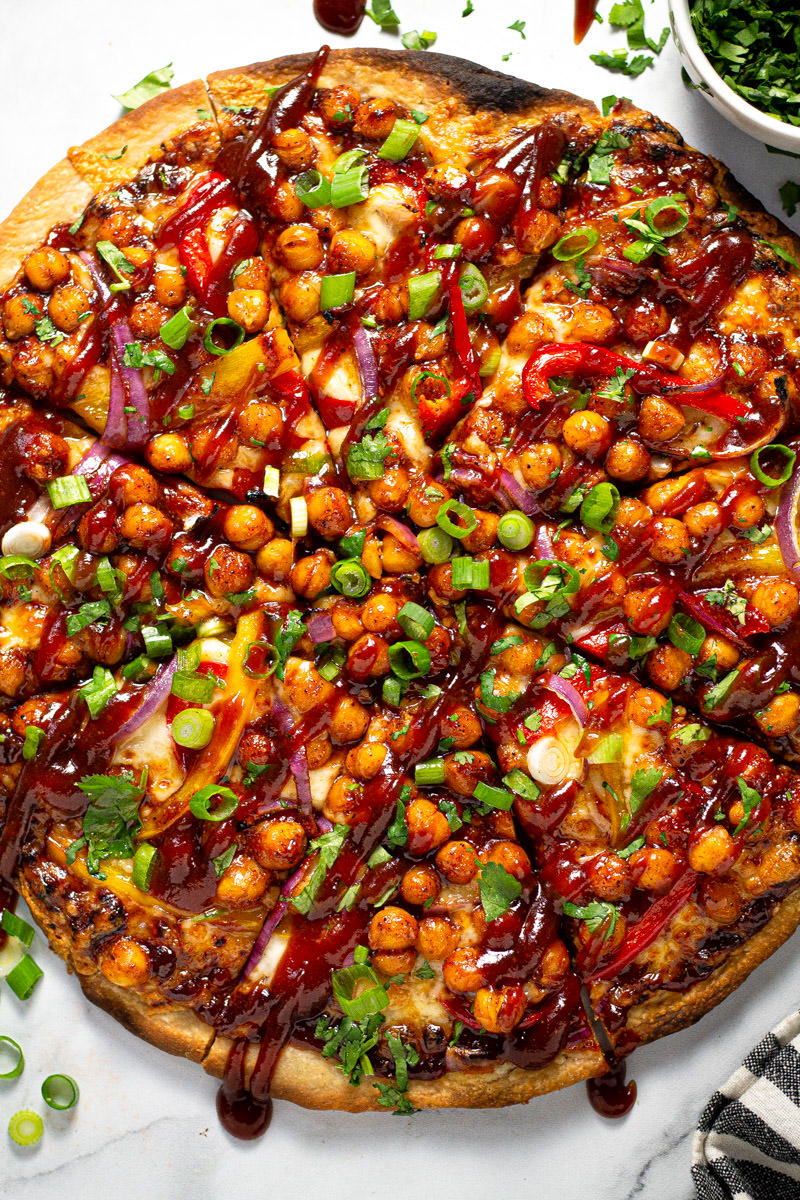 White marble counter top with barbecue chickpea pizza garnished with fresh cilantro