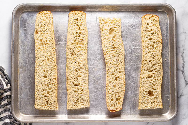 Baking sheet with sliced French bread on it