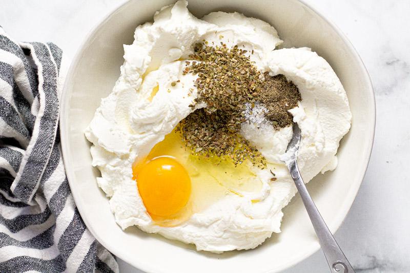 White bowl with ricotta oregano salt pepper and an egg