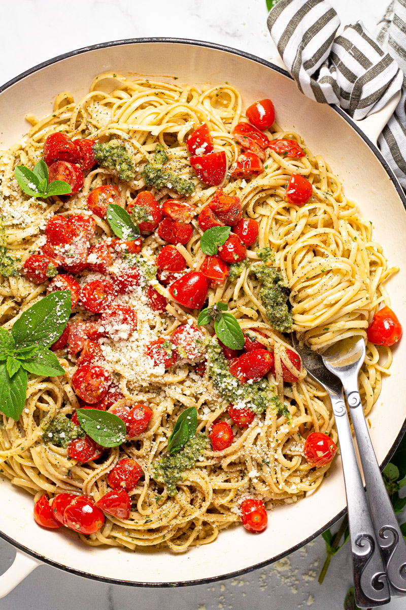 Large white pan filled with linguine tossed in a creamy pesto sauce with tomatoes