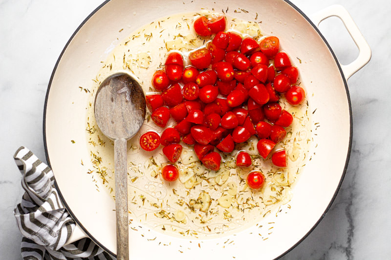 Large white pan with olive oil dried herbs and halved grape tomatoes
