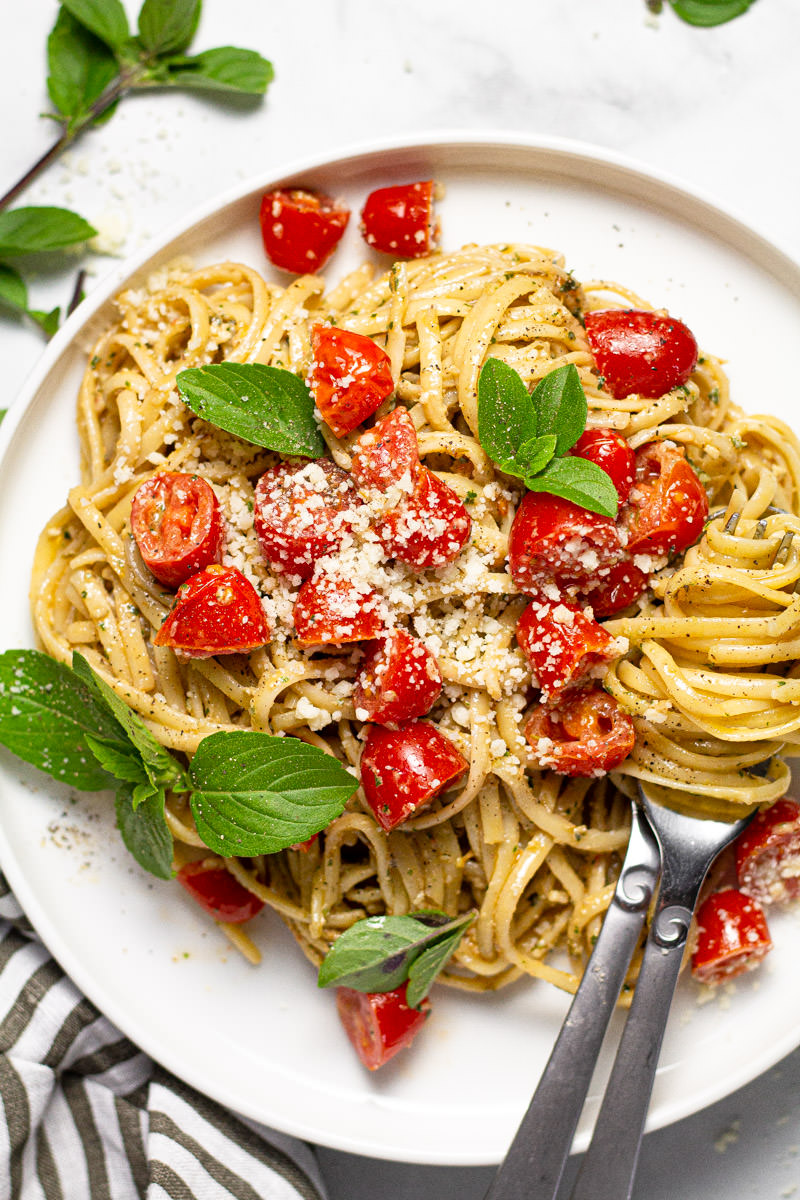 White plate with linguine tossed in a creamy pesto sauce with tomatoes
