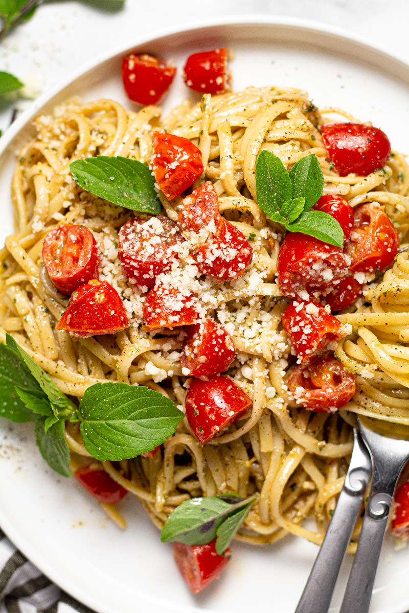 White plate with creamy pesto pasta with tomatoes