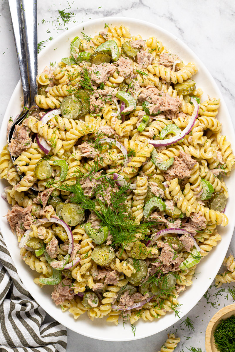 Large white platter filled with homemade tuna pasta salad garnished with fresh dill