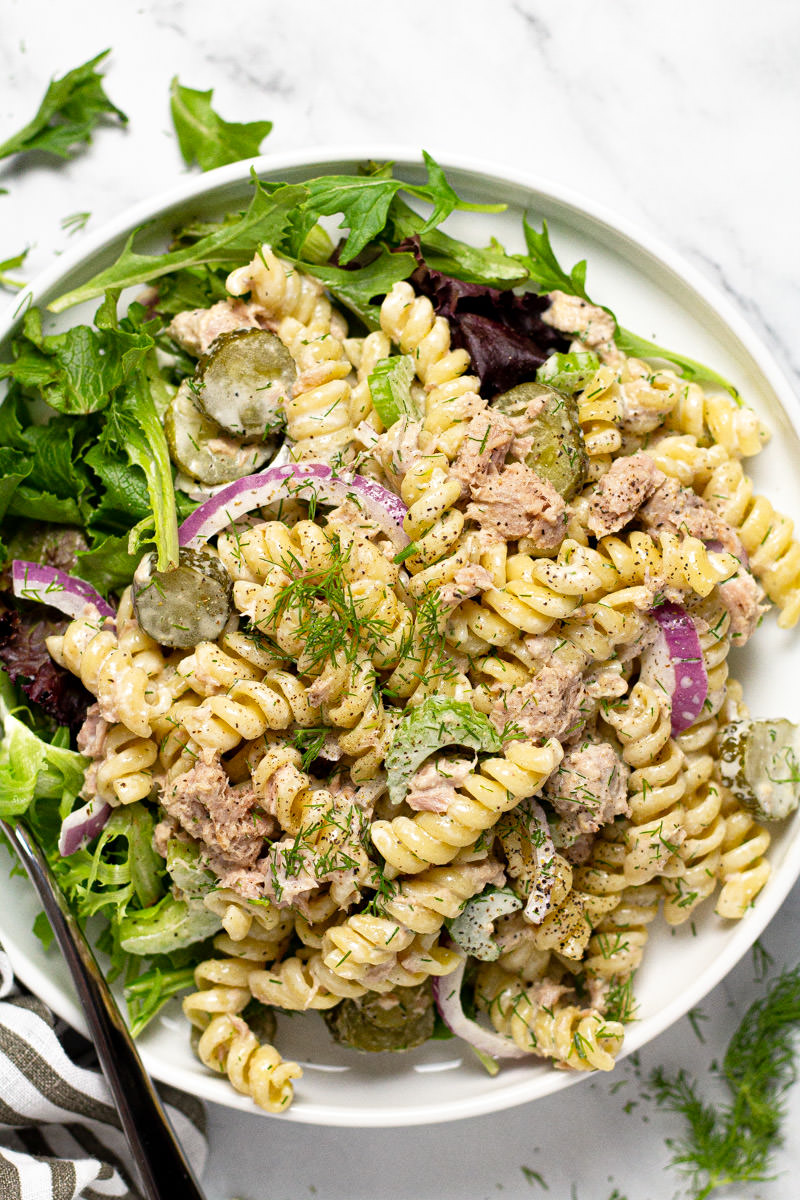 White plate filled with homemade tuna pasta salad garnished with fresh dill