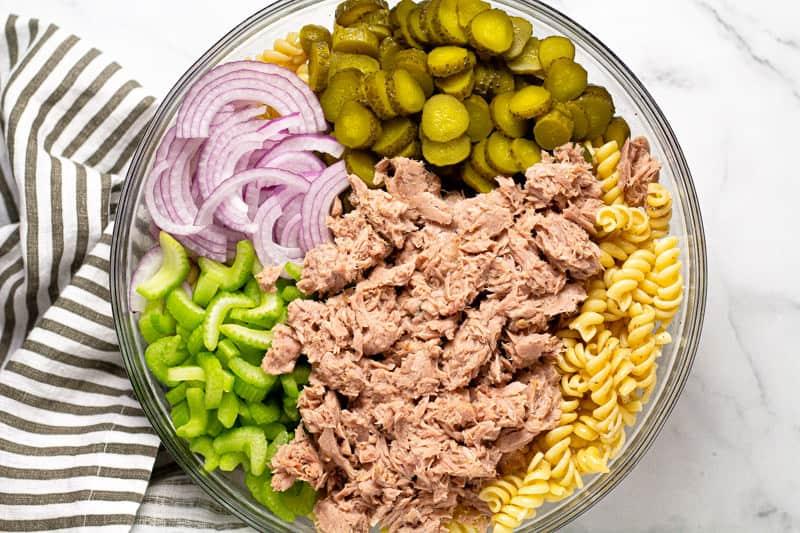 Large glass bowl with ingredients to make tuna pasta salad