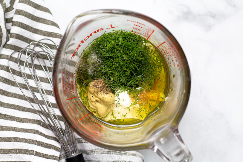 Overhead shot of a measuring cup with ingredients to make dressing for tuna salad