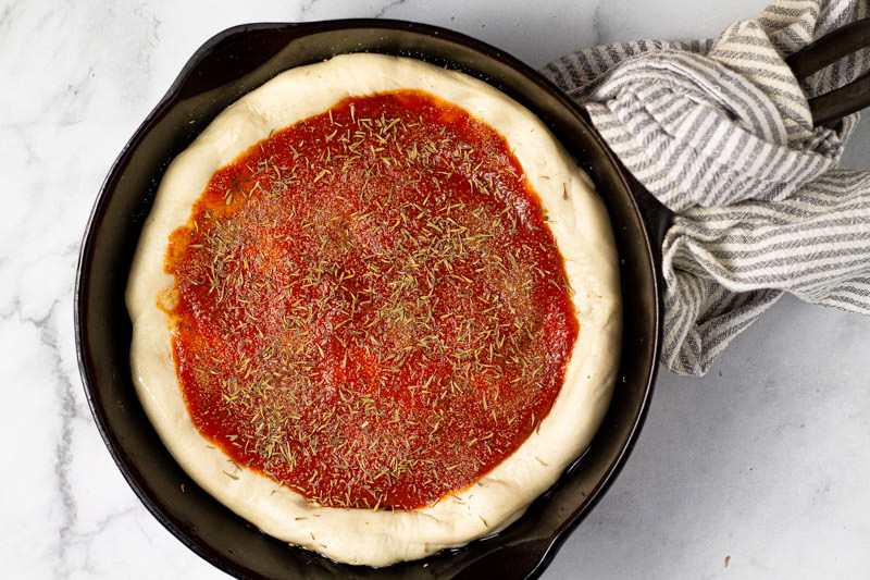 Pizza dough with pizza sauce and dried herbs in a cast iron skillet