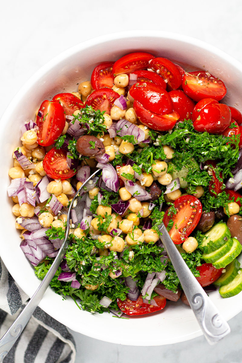 Large white bowl with Greek chickpea salad garnished with fresh parsley