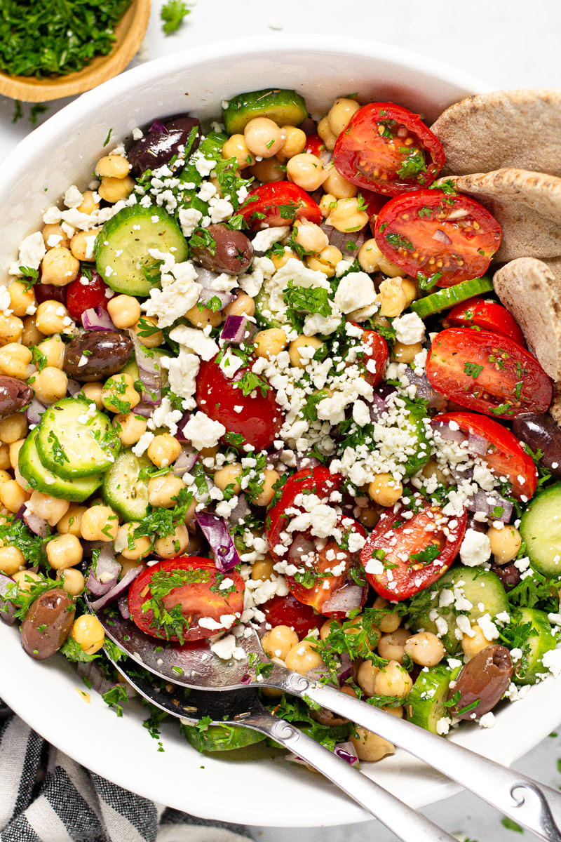 Large white bowl with Greek chickpea salad garnished with fresh parsley and feta