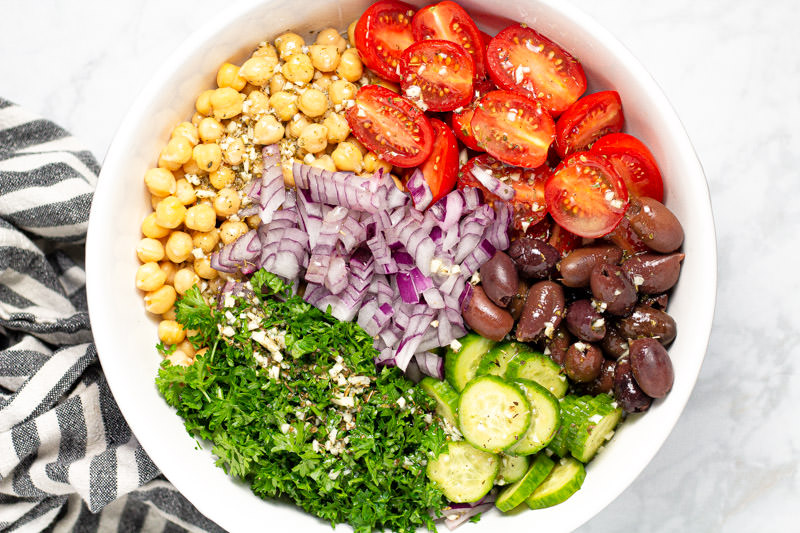 White bowl filled with ingredients to make a Mediterranean chickpea salad