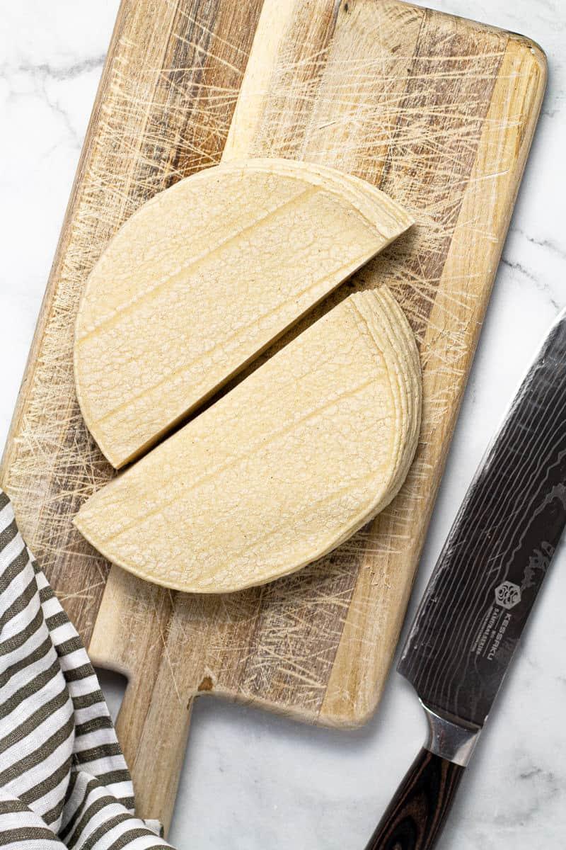 Small cutting board with corn tortillas cut in half
