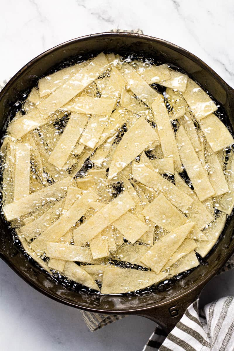 Cast iron pan with tortilla strips frying in oil