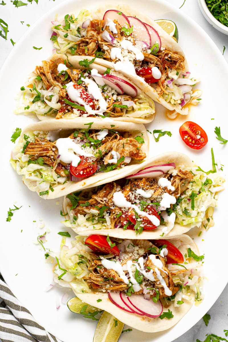 Large white platter with shredded chicken tacos garnished with sour cream and cilantro