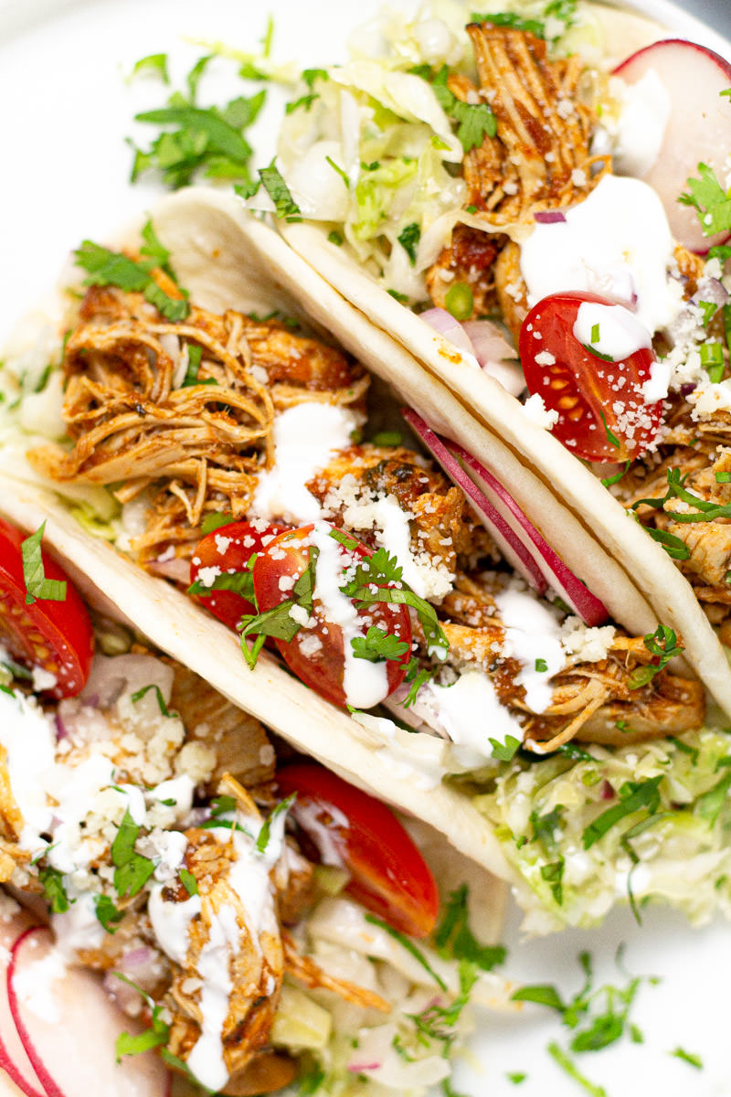 Close up shot of a white plate with shredded chicken tacos garnished with sour cream and cilantro