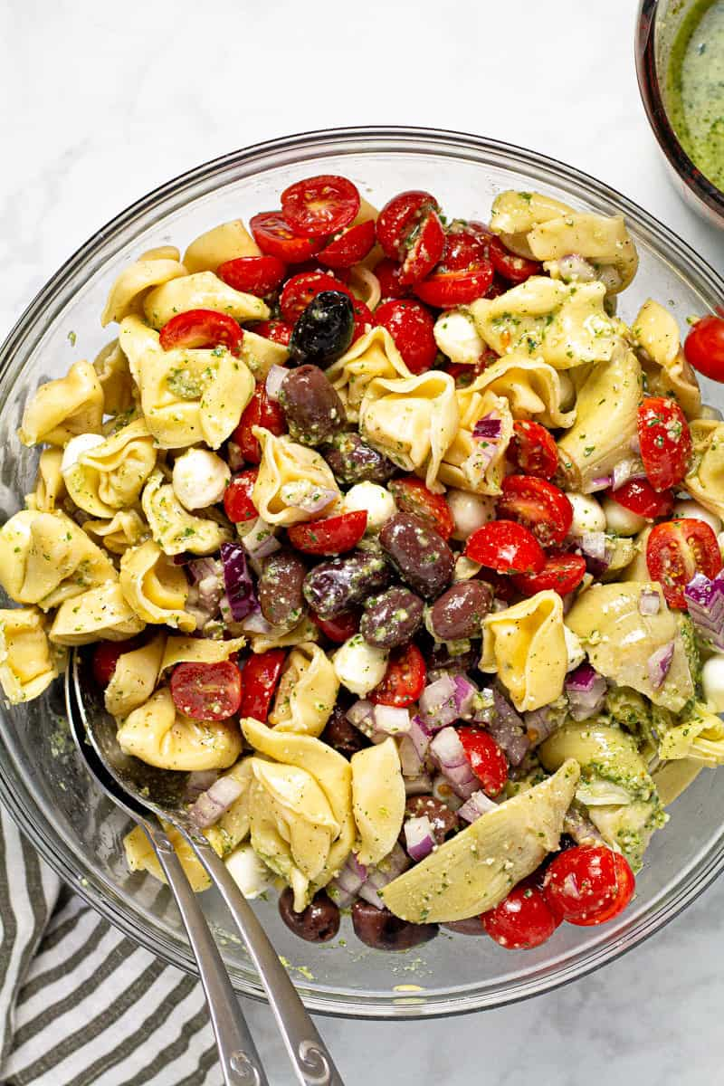 Large glass bowl filled with ingredients to make basil pesto pasta salad