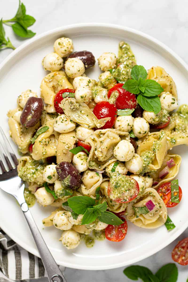 White plate with pesto pasta salad garnished with fresh basil