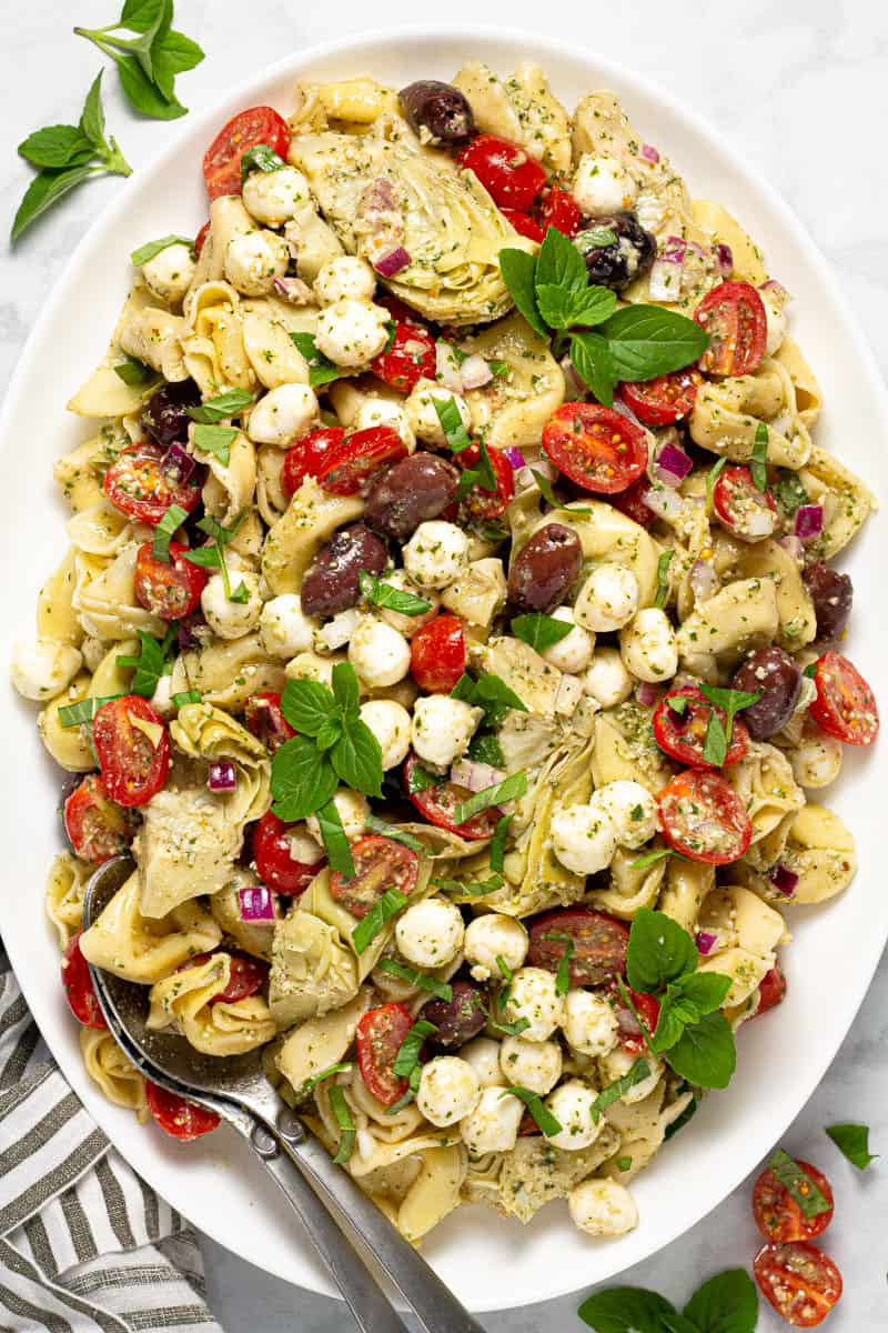 Large white platter with pesto pasta salad garnished with fresh basil