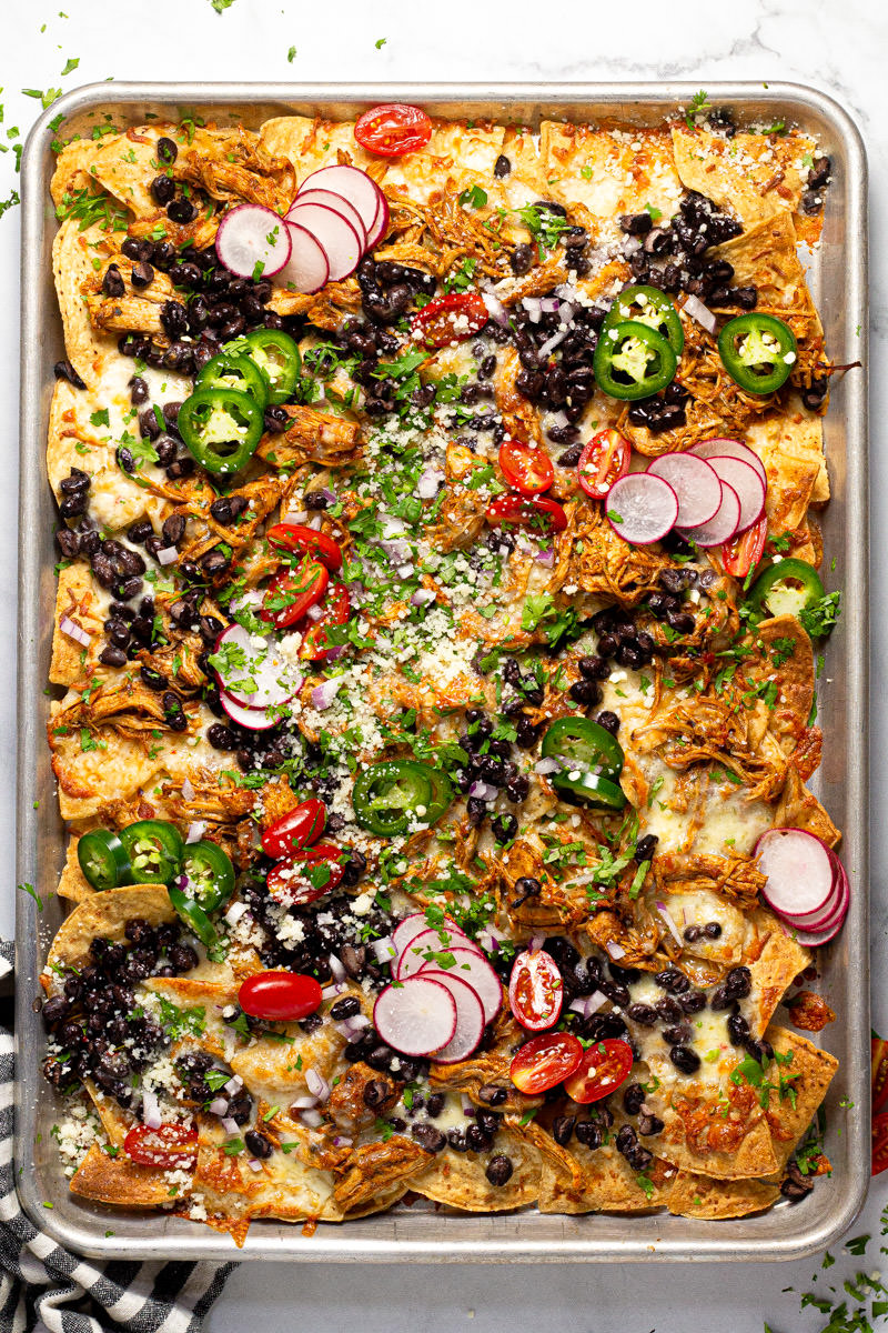 Sheet pan chicken nachos garnished with fresh cilantro and veggies