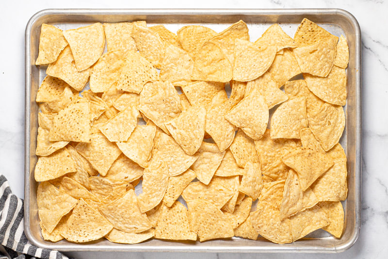 Baking sheet pan with tortilla chips spread in a layer on it