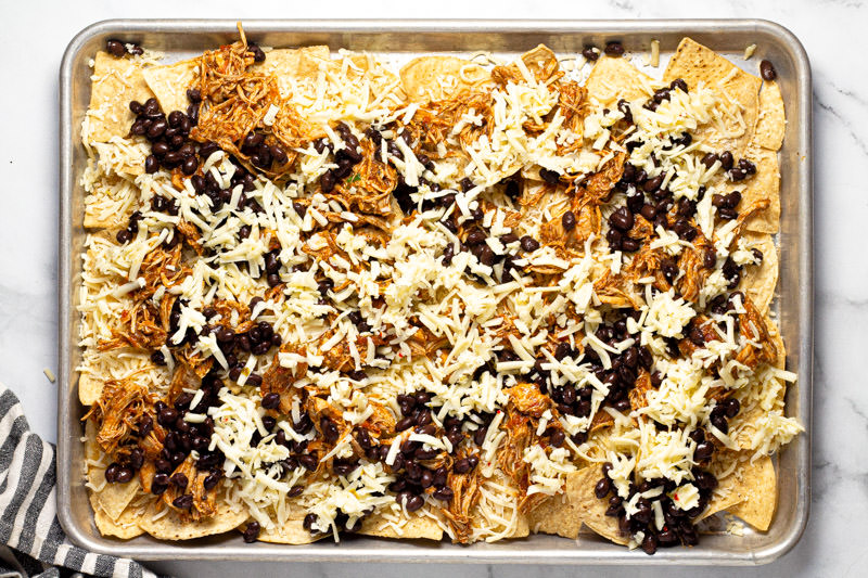 Baking sheet pan with tortilla chips shredded cheese chicken and black beans