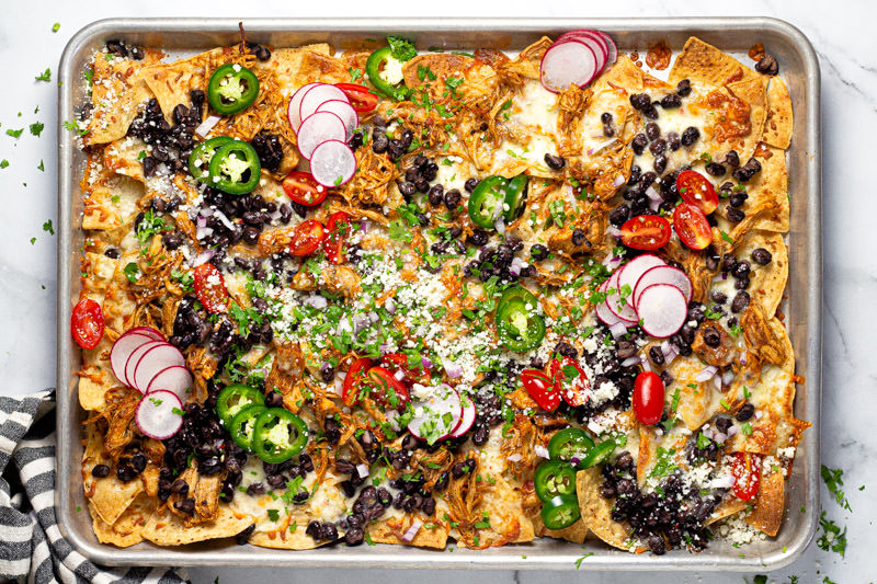 Overhead shot of sheet pan chicken nachos garnished with fresh cilantro and veggies