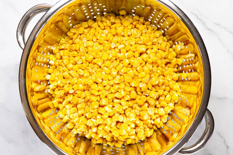 Metal strainer with kernels of sweet corn in it