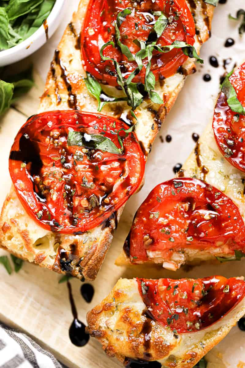 Close up shot of tomato mozzarella garlic cheese bread drizzled with balsamic and garnished with basil