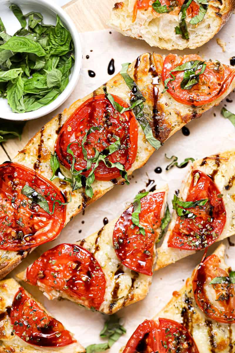 Tomato mozzarella garlic cheese bread drizzled with balsamic and garnished with basil