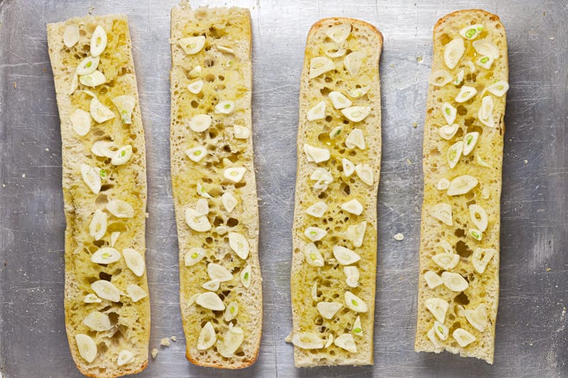 4 halves of French bread on a baking sheet with garlic and olive oil